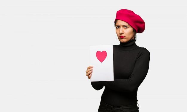 La giovane donna nell'incrocio di giorno di biglietti di s. valentino arma rilassato