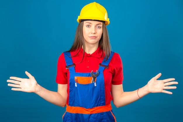 La giovane donna nell'uniforme della costruzione e nell'espressione clueless e confusa del casco di sicurezza giallo con le armi e le mani hanno sollevato la condizione sul fondo blu