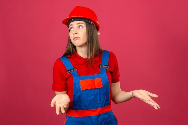 La giovane donna nell'uniforme della costruzione e nell'espressione clueless e confusa del casco di sicurezza rosso con le armi e le mani hanno sollevato la condizione sul fondo rosa scuro