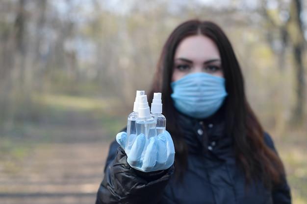 La giovane donna nella maschera protettiva mostra le bottiglie dello spruzzo del disinfettante all'aperto nel legno di primavera