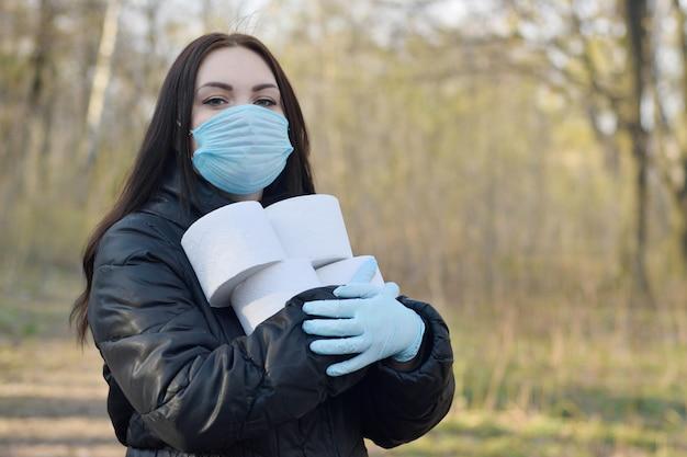 La giovane donna nella mascherina protettiva tiene molti rotoli di carta igienica