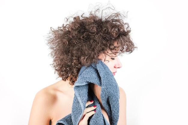La giovane donna nuda con capelli ricci pulisce il suo fronte con l'asciugamano contro il contesto bianco