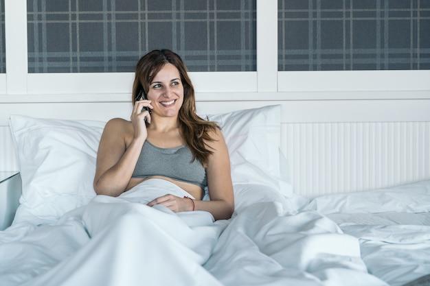 La giovane donna parla al telefono cellulare quando si sveglia nel suo letto.