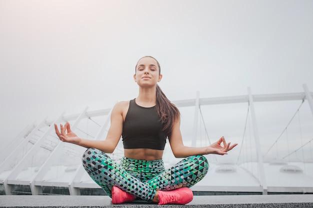 La giovane donna piacevole e allegra si siede nella posizione di loto e tiene le mani sulle ginocchia
