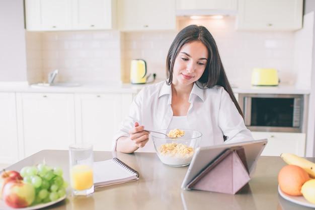 La giovane donna piacevole e positiva si siede al tavolo in cucina e mangia.