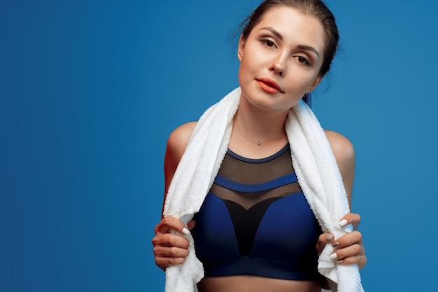 La giovane donna piacevole nello sport copre la tenuta dell'asciugamano in palestra