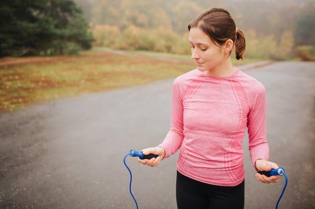 La giovane donna piacevole sta sulla strada e tiene la corda di salto. lei guarda in basso. la donna ben educata e magra è sola.