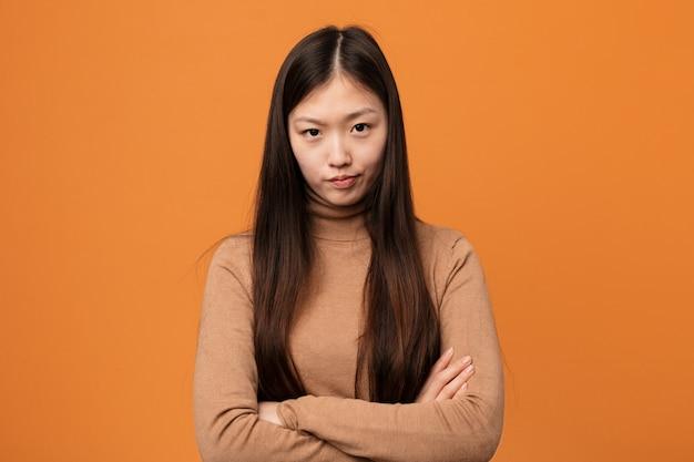 La giovane donna piuttosto cinese che aggrotta le sopracciglia con disappunto, tiene le braccia conserte.