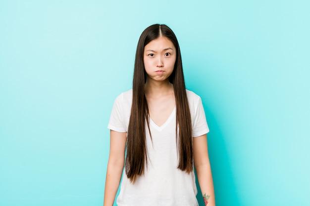 La giovane donna piuttosto cinese soffia sulle guance, ha un'espressione stanca. concetto di espressione facciale.