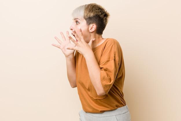 La giovane donna plus size con i capelli corti grida forte, tiene gli occhi aperti e le mani tese.