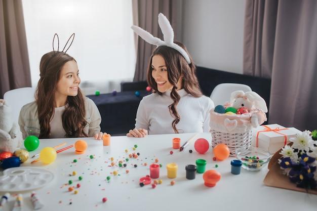 La giovane donna positiva piacevole e sua figlia si preparano per pasqua. stanno dietro il tavolo nella stanza e si guardano l'un l'altro. sorriso di madre e figlia. indossano orecchie da coniglio.