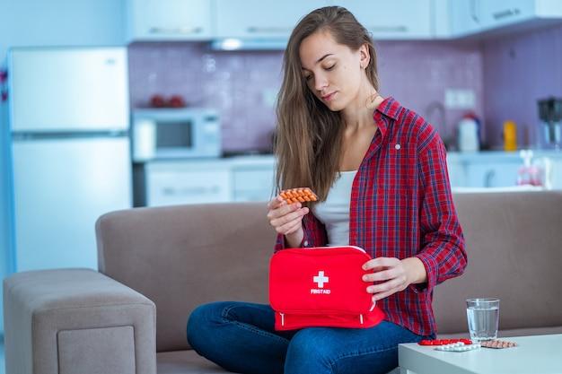 La giovane donna prende la medicina a casa. kit di pronto soccorso medico con pillole di malattie e dolori