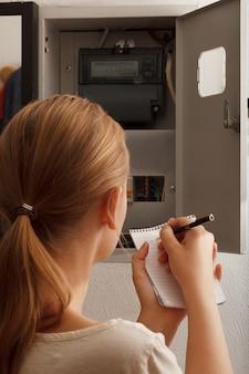 La giovane donna riscrive le letture del contatore elettrico