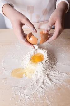 La giovane donna rompe l'uovo sopra la farina bianca per fare un impasto per pasta italiana, per ravioli o tagliatelle