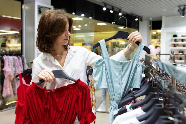 La giovane donna sceglie tra vestito rosso e blu nella sala commerciale del negozio di vestiti.