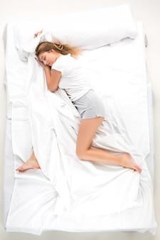 La giovane donna sdraiata in un letto
