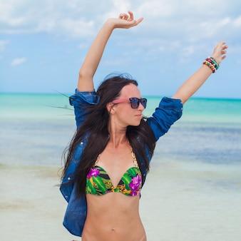 La giovane donna sexy in costume da bagno e giacca di jeans si diverte sulla spiaggia
