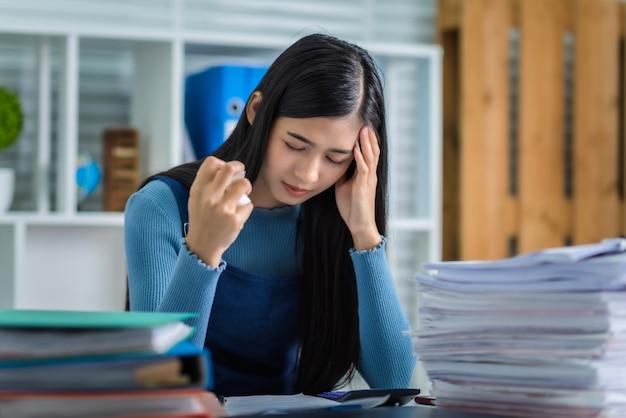 La giovane donna si è stancata di lavorare con la pila di documenti di contabilità di rapporti finanziari e servizio fiscale, carta sgualcita tenuta femminile attraente.
