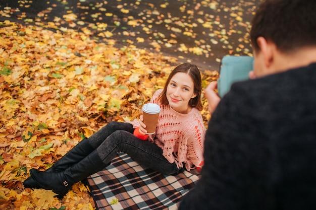 La giovane donna si siede sulla coperta su terra e posa sulla macchina fotografica. tiene in mano una tazza di caffè. il giovane in abiti neri le fotografa.