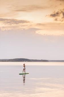 La giovane donna sopra sta sulla tavola da sup della pagaia con i bei colori del tramonto o dell'alba