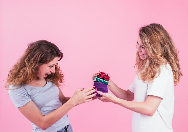 La giovane donna sorpresa che esamina il contenitore di regalo tiene dal suo amico