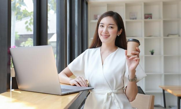 La giovane donna sorride e tiene la tazza di caffè mentre lavora con il computer portatile