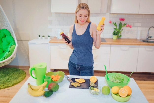 La giovane donna sorridente attraente tiene le bevande fresche della disintossicazione in bottiglie mentre cucina la frutta fresca e l'insalata nella cucina