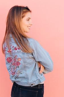 La giovane donna sorridente bionda con le sue armi ha attraversato contro fondo rosa