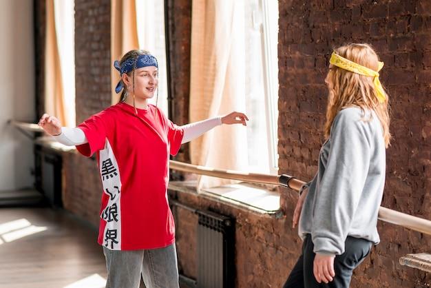 La giovane donna sorridente che mostra la sua danza fa un passo al suo amico