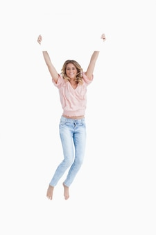 La giovane donna sorridente che salta mentre tiene un manifesto in bianco