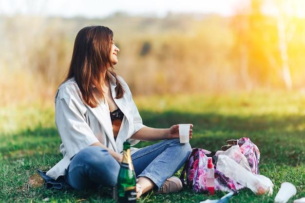 La giovane donna sorridente che si siede sull'erba e sul vino bevente, gode dell'estate della natura