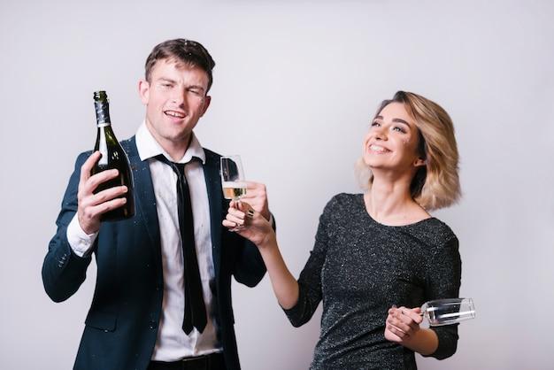 La giovane donna sorridente con i vetri si avvicina all'uomo con la bottiglia della bevanda
