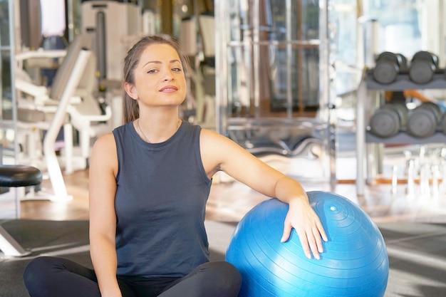 La giovane donna sorridente felice del primo piano in abiti sportivi, si siede sul pavimento con la palla per forma fisica, all'interno.