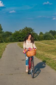 La giovane donna sorridente guida una bicicletta con un cesto pieno di fiori in campagna