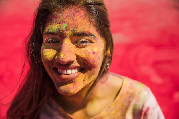 La giovane donna sorridente ha coperto il suo fronte di colore di holi che esamina la macchina fotografica