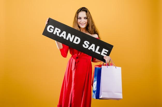 La giovane donna sorridente ha il grande segno di vendita con i sacchetti della spesa variopinti isolati sopra giallo
