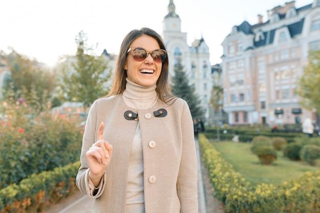 La giovane donna sorridente mostra il dito indice su