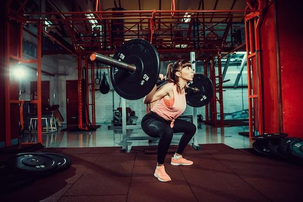 La giovane donna splendida di forma fisica si accovaccia e facendo l'esercizio della squadra con una barra dietro il collo in palestra.