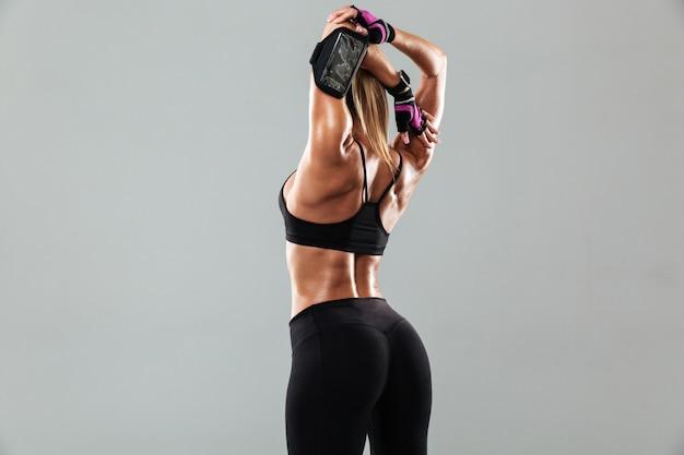 La giovane donna splendida di sport fa gli esercizi di sport