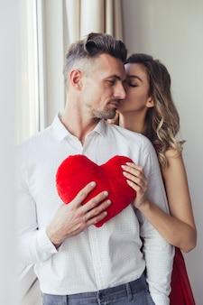 La giovane donna splendida in vestito rosso bacia il suo uomo e tiene il cuore del giocattolo della peluche