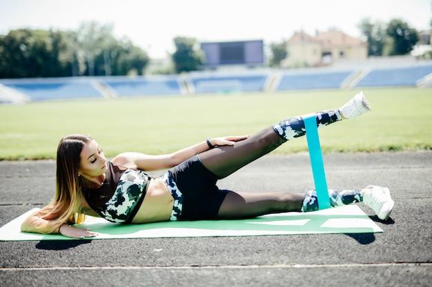 La giovane donna sportiva che fa gli esercizi con l'elastico all'aperto alla pista dello stadio.