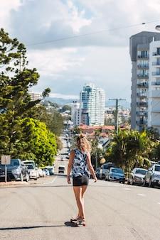 La giovane donna sportiva che guida sullo skateboard sulla strada è tornata.