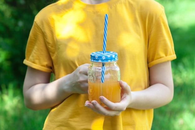 La giovane donna sta bevendo un gustoso frullato in barattolo di vetro con cannuccia
