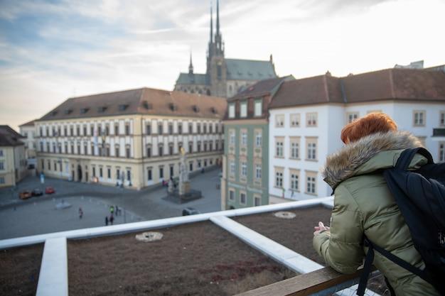 La giovane donna sta guardando brno da una terrazza panoramica. scatta foto della città al telefono e condividila sul sito social
