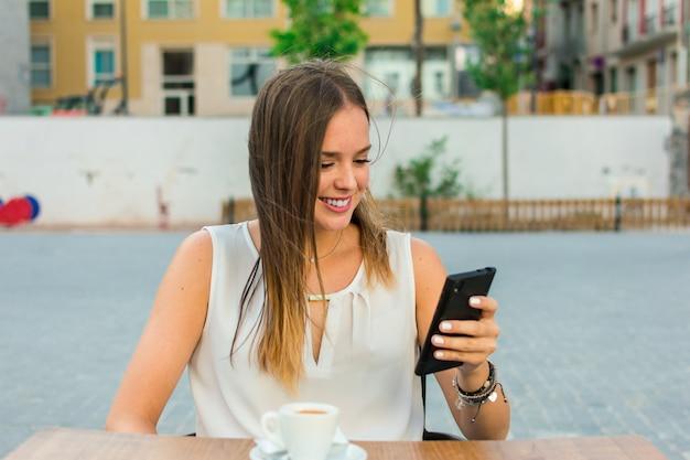La giovane donna sta guardando mobile mentre sta prendendo il caffè
