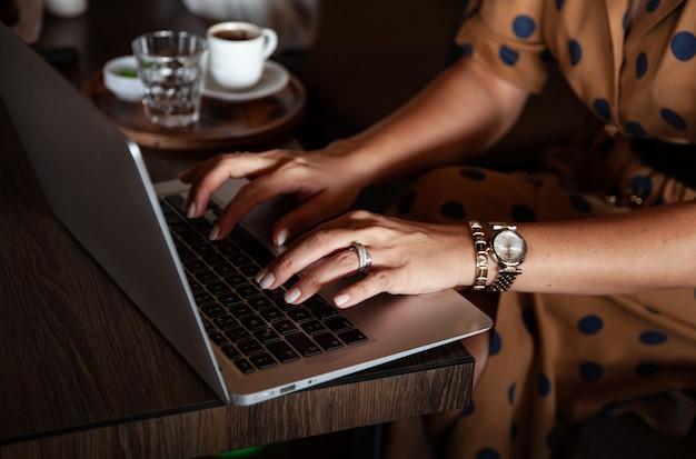 La giovane donna sta lavorando al computer, digitando sul computer portatile nella caffetteria