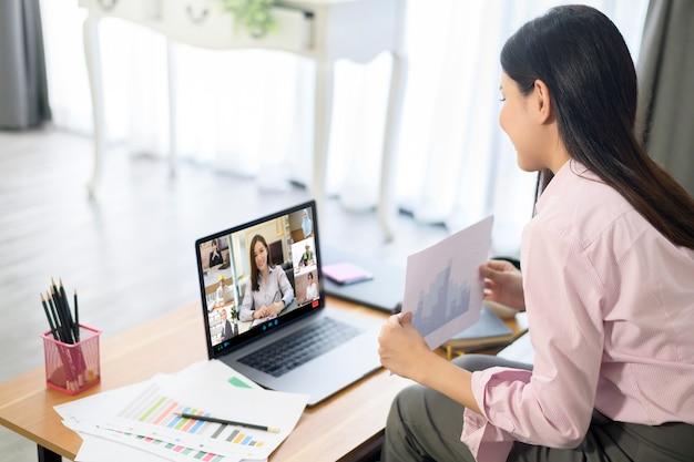 La giovane donna sta lavorando con lo schermo del computer durante la riunione di lavoro tramite l'applicazione di videoconferenza.