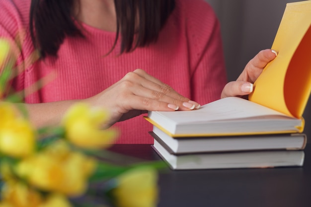 La giovane donna sta leggendo un libro a casa. sfondo sfocato orizzontale, effetto film.