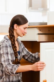 La giovane donna sta montando un armadio