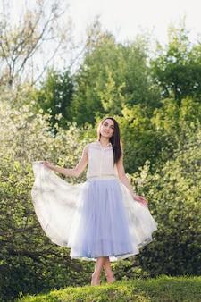 La giovane donna sta su una collina sullo sfondo di alberi in fiore